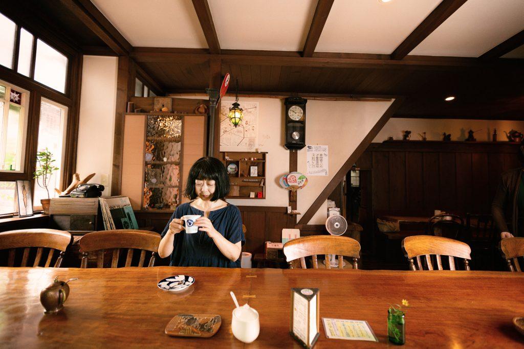喫茶「トンボロ」のテーブルに座るこがしわかおりさん