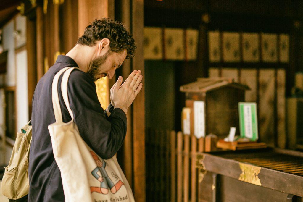 神社で拝むアレッサンドロさん